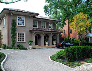 The right direction. The curve in the driveway downplays the service entrance to the left. Cobblestone inlay gently guides you to the front of the house. The columnar sweetgum lends a Mediterranean accent.