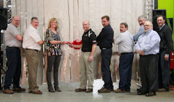 Cutting the ribbon, from left, are Line Supervisor Chris Gruss, Tree Care Products Sales Manager Casey Gross, VP of Finance Debbie Lehmann, Product Manager Jason Showers, Welder Mike Jolman, Engineer Craig Swan, Engineering Manager Larry Voelker, and President Jim Shoemaker Jr. Standing in front of Voelker and Shoemarker is Jim Bardos, manager and operation engineer.