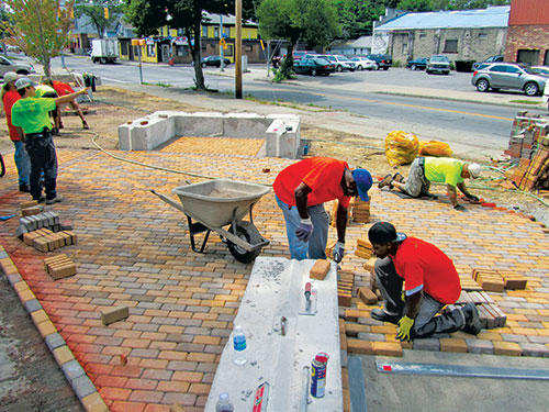 Local residents install pavers at Project Scion: The Orchard. Photo: Zaretsky & Associates
