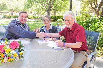 From left to right: Jim Ingram, Nelda Matheny and Jim Clark shaking hands