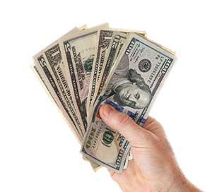 A hand holding cash. Image: iStock.com/Fotonen