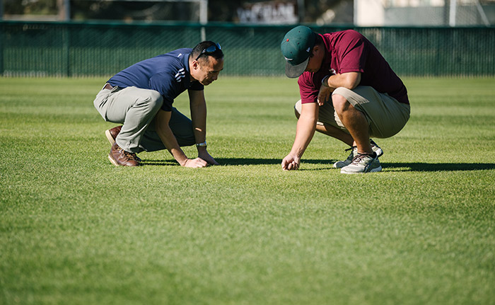 Gil Del Rosario (left) discusses turf management with a sports turf manager. (Photo: Corteva Agriscience™, Agriculture Division of Dow DuPont)