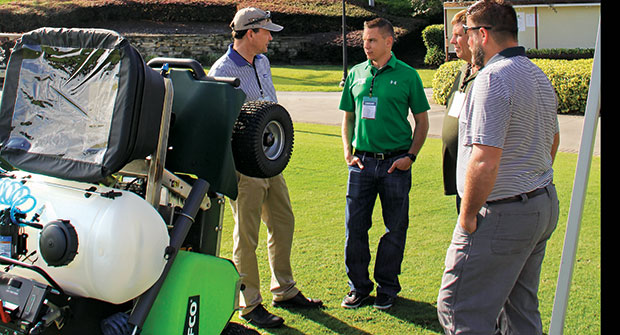 Turfco President George Kinkead (left) talks to the Spring Touch Lawn & Pest Control team about the finer details of the T3100 spreader-sprayer. (Photo: Seth Jones)