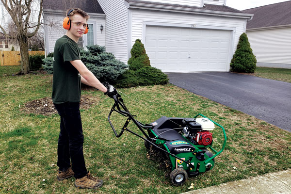 Grant Weckerly, a scout with Troop 318 in Delaware, Ohio, stands with a Ryan Lawnaire V aerator loaned by Hayward Distributing Co. Photo: Craig Myers