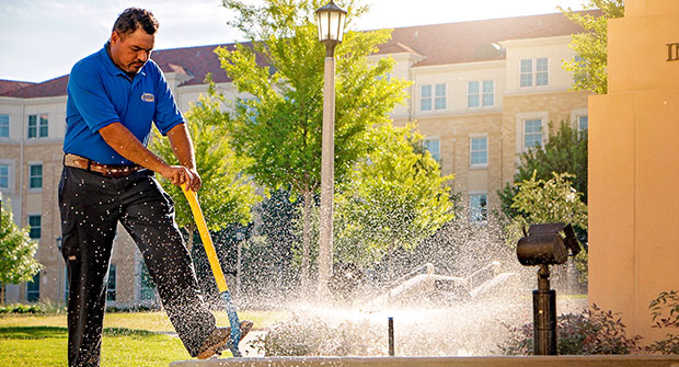 Crew member working at TCU (Photo: Andy's Sprinkler, Drainage & Lighting)
