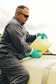 Man pouring chemicals (Photo: Dow Agrisciences)