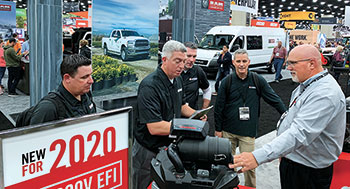 Darrell Hyde shows off Kawasaki Motors Corp.'s new FX 100 EFI engine to LM's Dan Hannan, Seth Jones, Craig MacGregor and Bill Roddy. (Photo: LM Staff)