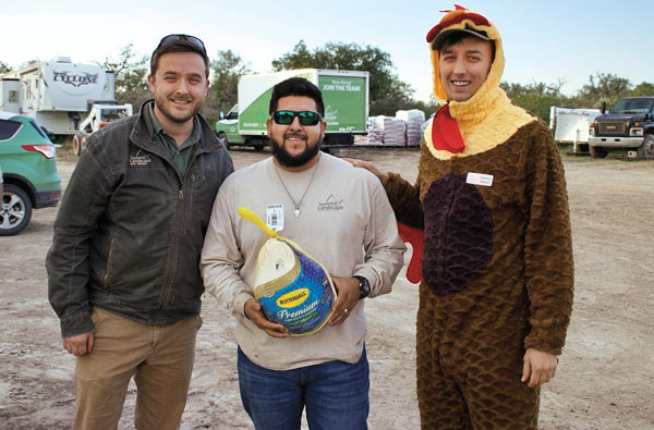 Gobble, gobble! At Summit Landscape and Design, Hondo, Texas, the company president, Josiah Peterson (left), gets the help of a feathered friend to hand out turkeys to his employees in honor of the Thanksgiving holiday. (Photo: Summit Landscape and Design)