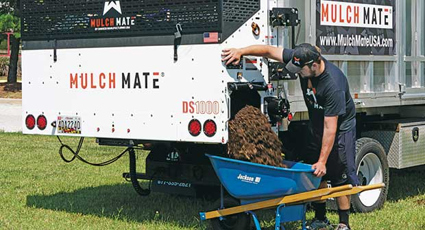 Person filling wheelbarrow using Mulch Mate (Photo: Mulch Mate)