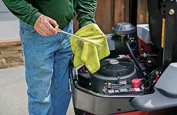 Person performing engine maintenance (Photo: Exmark)