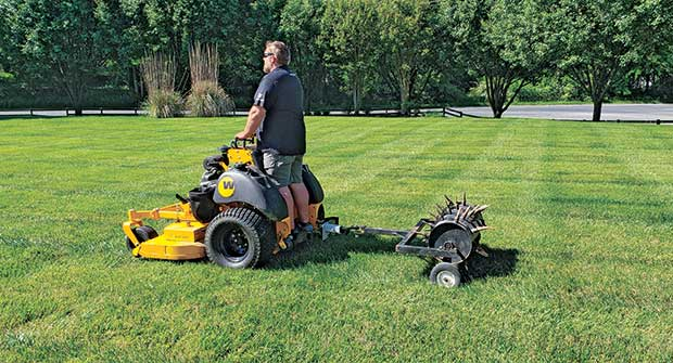 Person using tow-behind aerator (Photo: Mulch Mate)