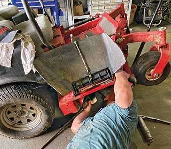 Person servicing mower (Photo: Froio Lawn & Landscape)