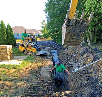 Crew members working with tracked machine (Photo: Turf Management Services)