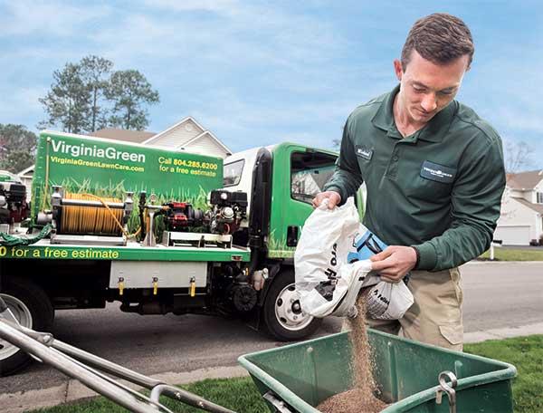 Crew member pouring fertilizer into spreader (Photo: Tony Ventouris)