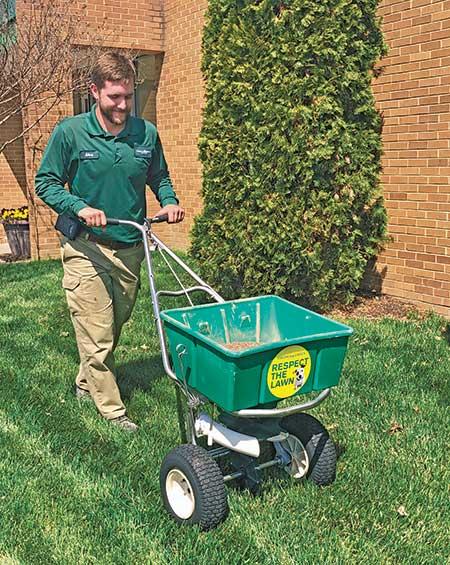 Crew member spreading fertilizer (Photo: Virginia Green Lawn Care)