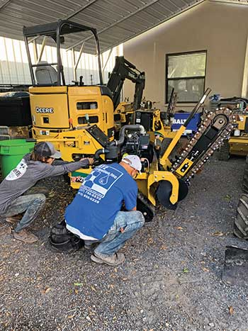 People servicing a trencher (Photo: Tom Zullo/ATZ Irrigation)