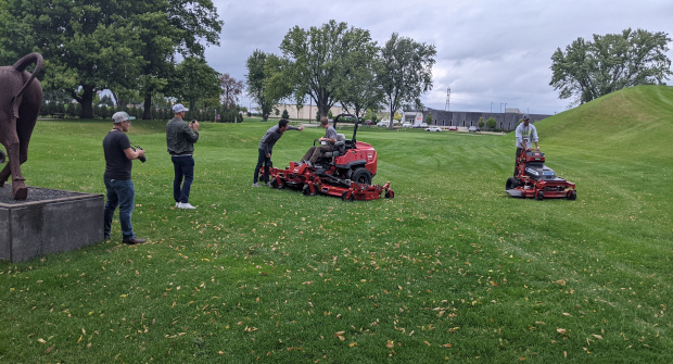 Visitors to Toro's Minneapolis headquarters test the company's 144-inch zero-turn mower (left) and the GrandStand Revolution electric stand-on mower (right) (Photo: LM Staff).